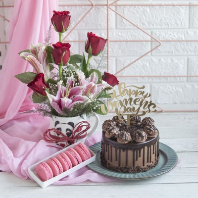 Ferrero Rocher chocolate cake 750gms with Happy Women,s Day Topper , box of 5 macarons and Arrangement of Red Roses and lilies in a mug