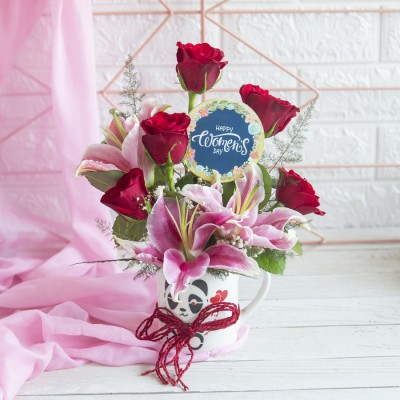 Arrangement of Red Roses and lilies in a mug with a Blue Women's Day Topper
