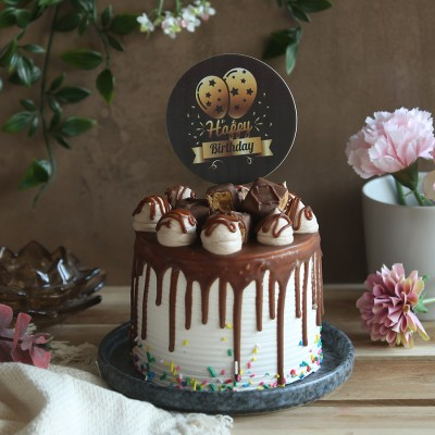 Chocolate Snickers Cake with happy birthday topper in black with balloons