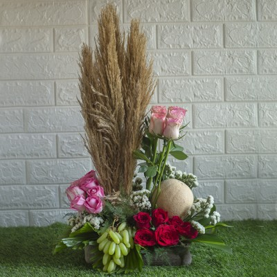 Arrangement of Grapes , Muskmelon, Red Roses , Pink Roses Jumelias, And Broom gloom in a  basket