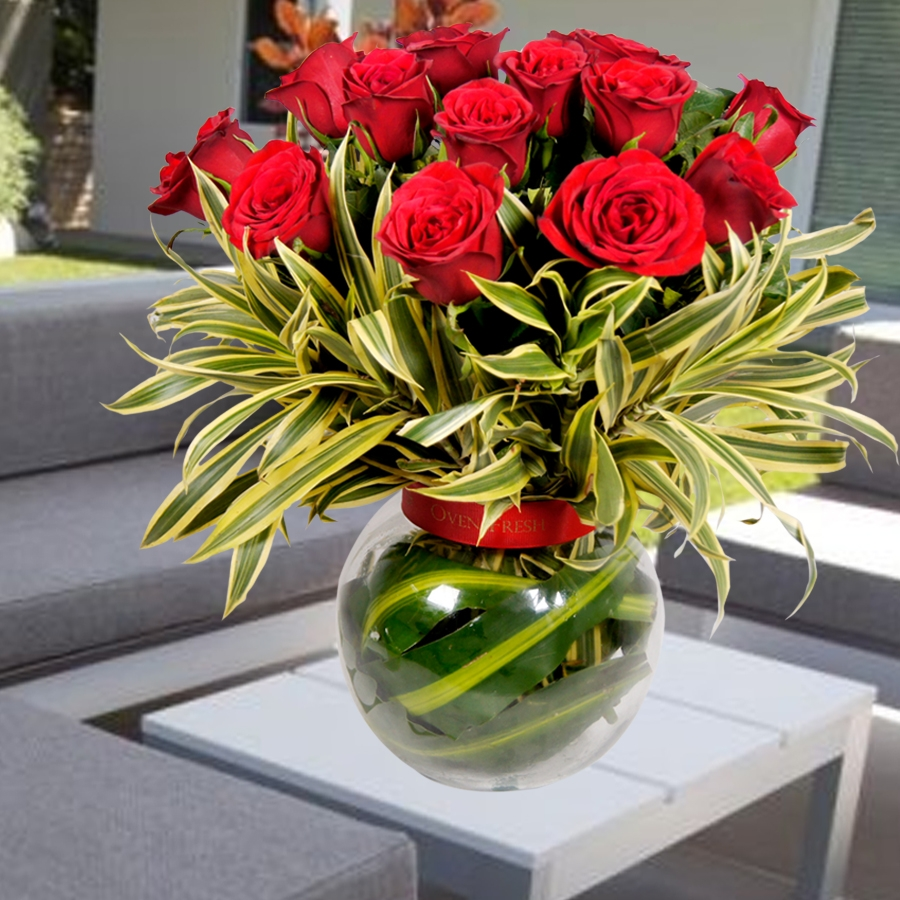 Glass pot with green leaves and roses